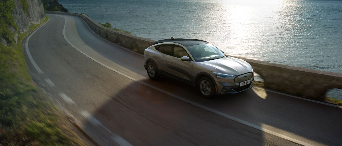Silver All Electric Ford Mustang Mach-E driving sunny cliffs and sea